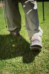 Womans feet in hiking boots walking on grass