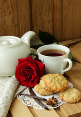 Still life with cup of tea, red rose and  oatmeal cookies.