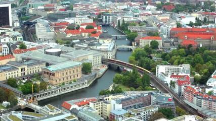 Berlin, train moves through river Spree on railway bridge