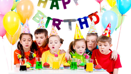 Group of kids blowing candles at the birthday party.