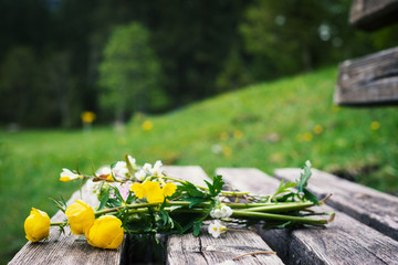 romantic bunch of yellow flowers on old wooden timber bench