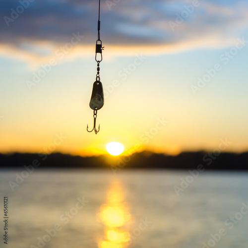 fishing on a lake before sunset - 65610121