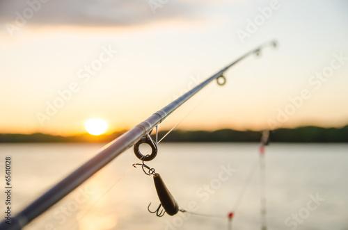 fishing on a lake before sunset - 65610128
