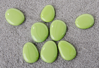 Composition of green pebbles on the sand