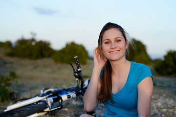 healthy cheerful young woman riding mountain bike in countryside