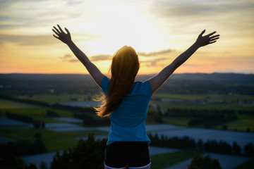happy young woman outdoor rising hands and looking at sunset
