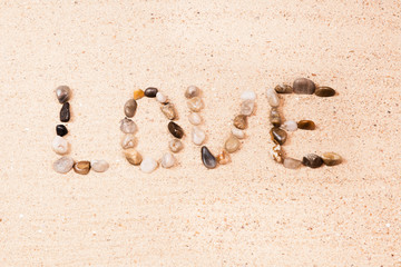 word love written with pebbles on the sand of a beach