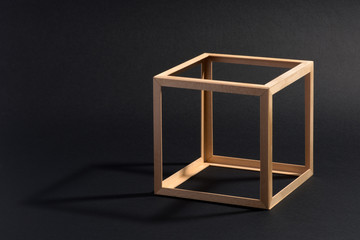 Open frame wooden cube on black
