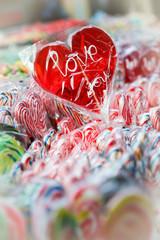 Red heart lollipop, with candies around.
