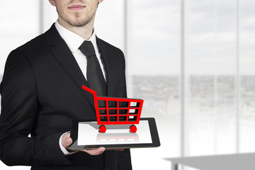 businessman holding tablet red cart standing in office