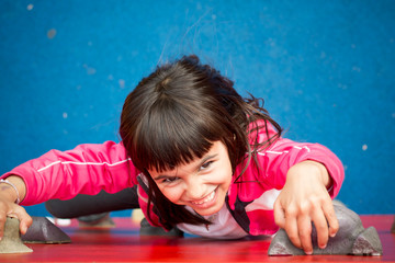 Pretty girl climbing a red wall in a playground