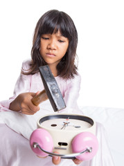 Irritated young  girl waking up from sleep and destroy clock