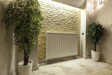Modern radiator mounted on brick wall