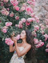 Young woman among roses in a garden