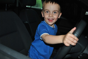 A young child driving a car