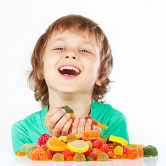 Smiling child with sweets and candies on a white background