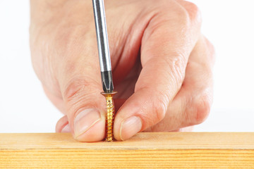 Screwing screws in a wooden block with a screwdriver
