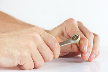 Hand of repairman with a wrench to tighten the nut
