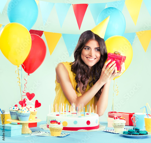 Beautiful woman holding a present at her birthday party - 65623767