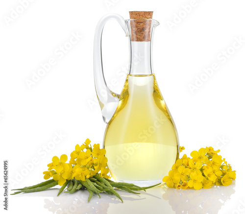 Rapeseed oil and flowers isolated over white. - 65624995