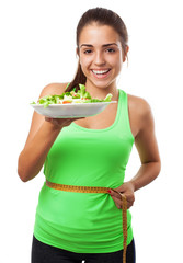 young sporty woman measuring herself and holding a salad on whit