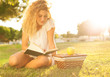pretty blond young woman reading a book at park