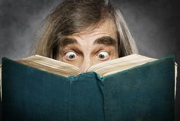 Senior reading open book, suprised old man,  amazing eyes