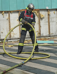 pompier manipulant un tuyau d'incendie