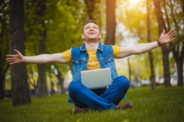 young man in the park with a laptop
