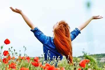 redhead girl in field is enjoying sun