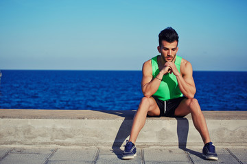 Attractive jogger sits on a beautiful sea background
