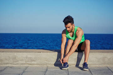 Sporty guy jogging sitting strikes up shoelaces