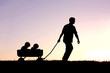 Silhouette of Father Pulling Sons in Wagon at Sunset - 65630734