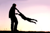 Silhouette of Father Playing with Child Outside at Sunset