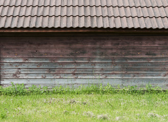 Old brown wooden wall with green grass as background