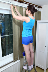 Girl installs dense fabric vertical blinds, click into place sla