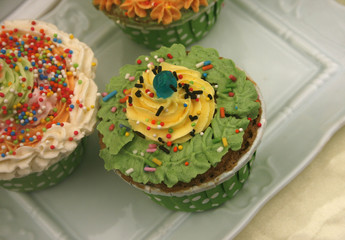 Closeup of assorted flavors of decorated cupcakes sitting on