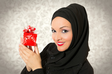 Model dressed in traditional Arabic style, holding present box