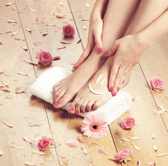 Spa compositions of sexy female feet  and pink petals
