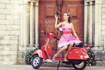 Young and sexy woman with a motor scooter - retro style image