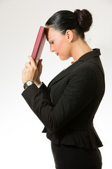 Black hair business dressed woman holding red book