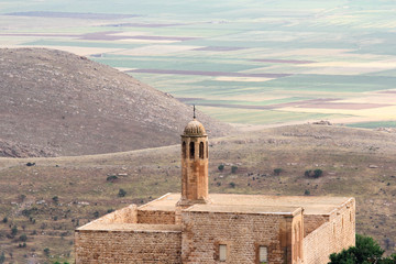 The mosque in Mardin and colorful field background,Turkey