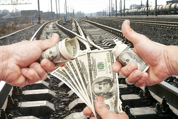 Hands with notes of dollars against the railroad