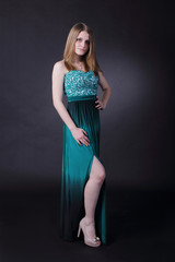 Mysterious girl in the emerald dress on a dark background