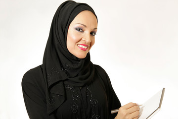 Arabic woman, traditional dressed, writing on blank paper