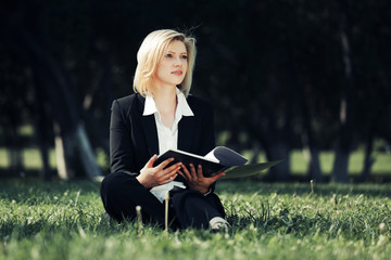 Young business woman with a folder in a city park