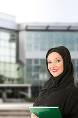 Arabic woman, traditional dressed, in front of office