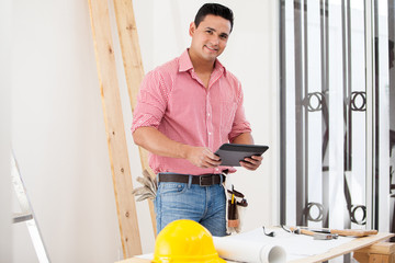 Happy contractor using a tablet