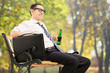 Businessman taking a break in park with a beer