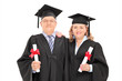 Mature couple in graduation gowns with diplomas